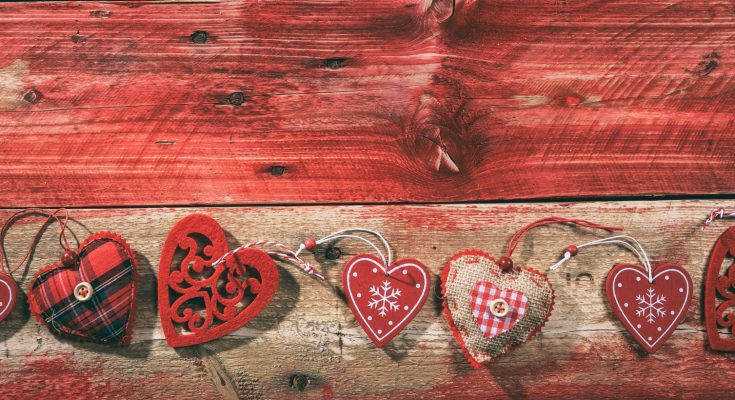 Decorative hearts on red wooden background